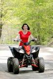 Donna nel colore rosso sul veicolo a quattro ruote Immagine Stock