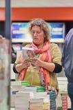 Donna nel deposito di libro esente da dazio all'aeroporto di Schiphol, Paesi Bassi Immagine Stock