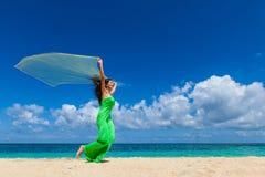 Donna nel funzionamento del vestito sulla spiaggia immagine stock