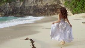 Donna nel funzionamento lungo del vestito sulla spiaggia che lascia le orme video d archivio