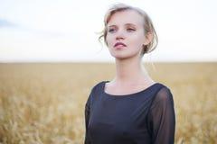 Donna nel giacimento di grano sotto il cielo grigio fotografia stock