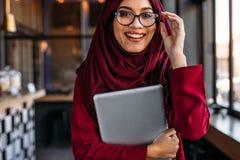 Donna nel hijab alla caffetteria con il computer portatile immagini stock libere da diritti