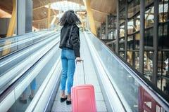 Donna nel marciapiede mobile all'aeroporto con una valigia rosa fotografie stock