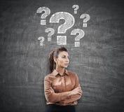 Donna nel marrone e punti interrogativi sulla lavagna Immagini Stock