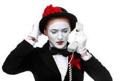 Donna nel mimo di immagine che tiene un microtelefono immagini stock