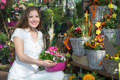 Donna nel negozio di fiore fra le disposizioni dei fiori fotografia stock libera da diritti