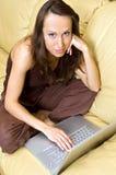 Donna nel paese con il computer portatile sul sofà Fotografia Stock Libera da Diritti
