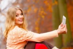 Donna nel parco di autunno facendo uso della compressa Immagini Stock
