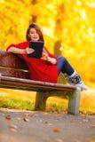 Donna nel parco di autunno facendo uso della lettura del computer della compressa Fotografia Stock Libera da Diritti