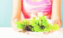 Donna nel piatto dell'insalata della tenuta del reggiseno di sport dopo il giorno di allenamento Concetto sano di stile di vita Immagine Stock