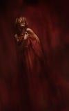 Donna nel rosso, capelli sul fronte, modello sensuale di modo di bellezza Immagine Stock