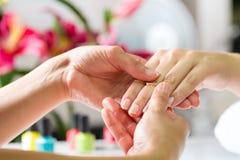 Donna nel salone del chiodo che riceve massaggio della mano Fotografia Stock