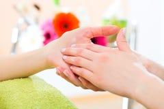Donna nel salone del chiodo che riceve massaggio della mano Immagine Stock Libera da Diritti