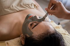 Donna nel salone della stazione termale che ottiene la maschera di protezione dall'estetista fotografia stock