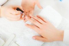 Donna nel salone di bellezza che ottiene manicure fatto Immagini Stock