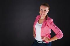 Donna nel siute rosa sopra sorridere scuro del fondo Fotografia Stock