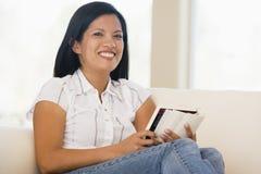 Donna nel sorridere del libro di lettura del salone Fotografia Stock Libera da Diritti