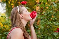 Donna nel suo giardino che fiuta alle rose Immagini Stock