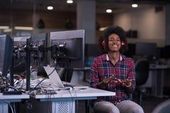 Donna nel suo luogo di lavoro in musi d'ascolto dell'ufficio di giovane impresa Fotografie Stock