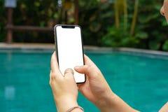 Donna nel telefono della tenuta dello stagno con uno schermo e una struttura moderna meno progettazione immagine stock libera da diritti