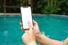 Donna nel telefono della tenuta dello stagno con uno schermo e una struttura moderna meno progettazione fotografie stock libere da diritti