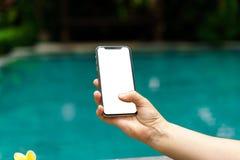 Donna nel telefono della tenuta dello stagno con uno schermo e una struttura moderna meno progettazione fotografia stock