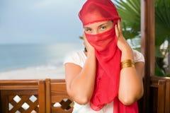 Donna nel yashmak che si siede in un supporto conico sul litorale Immagini Stock