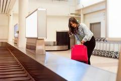 Donna nell'aeroporto che raccoglie i suoi bagagli all'area del nastro trasportatore Immagini Stock Libere da Diritti