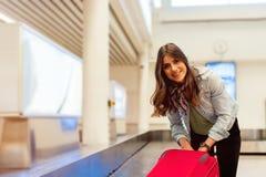 Donna nell'aeroporto che raccoglie i suoi bagagli all'area del nastro trasportatore Immagini Stock
