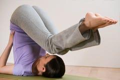 Donna nell'allungamento della posa di yoga Immagini Stock