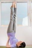 Donna nell'allungamento della posa di yoga Fotografie Stock