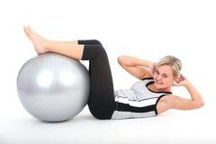 Donna nell'esercitazione dell'attrezzatura di ginnastica Fotografia Stock Libera da Diritti
