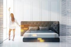 Donna nell'interno della camera da letto di mattina fotografia stock