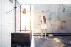 Donna nell'interno di marmo bianco del bagno del sottotetto immagini stock libere da diritti