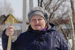 Donna nell'inverno nel paese con una pala per neve eliminante Fotografia Stock Libera da Diritti