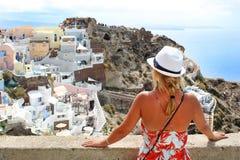 Donna nell'isola di Santorini, Grecia OIA, città di Fira Case e chiese tradizionali e famose sopra la caldera immagini stock libere da diritti