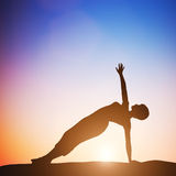 Donna nell'yoga laterale dell'equilibrio che medita al tramonto zen Fotografia Stock