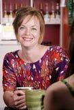 Donna nella casa di caffè con l'amico femminile Fotografia Stock