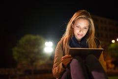 Donna nella città alla compressa della tenuta di notte, lettura qualcosa fotografia stock
