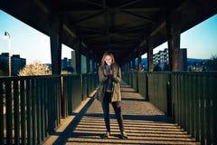 Donna nella città allo smartphone della tenuta di notte, mandante un sms Fotografia Stock