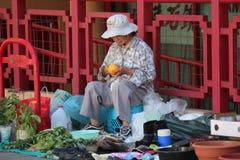 Donna nella città della Cina che vende le verdure Immagini Stock