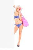 Donna nella condizione e nella holding del bikini un comitato Fotografie Stock