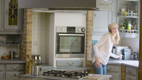 Donna nella cucina che ascolta la musica in sue cuffie che preparano e che aspettano caffè archivi video