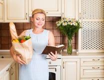Donna nella cucina con il sacchetto della spesa di carta pieno delle verdure immagini stock libere da diritti