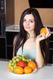 Donna nella cucina con la frutta Immagini Stock