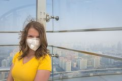 Donna nella maschera medica contro l'inquinamento atmosferico fotografia stock