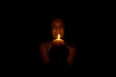 Donna nella nerezza con l'indicatore luminoso della candela fotografia stock