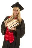 Donna nella pila nera dell'abito di graduazione di capovolgimento dei libri Fotografia Stock