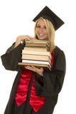 Donna nella pila nera della tenuta dell'abito di graduazione di libri Fotografie Stock