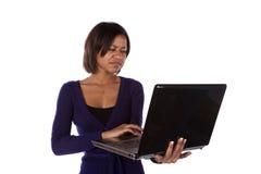 Donna nella porpora sul computer portatile frustrato Fotografia Stock